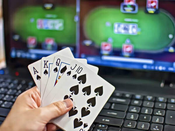 a person showing his cards in front of a laptop screen