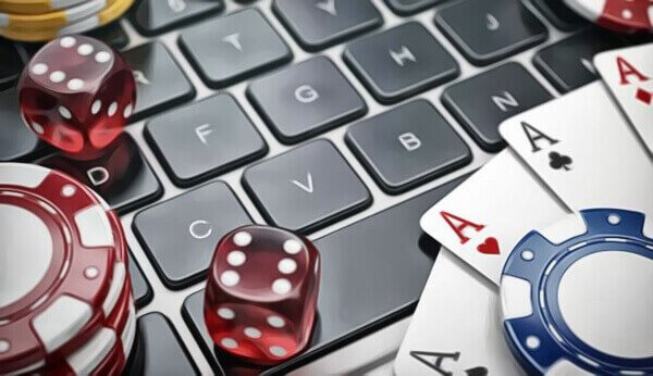 cards, dice, and poker chips on a laptop keyboard